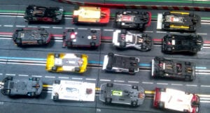Underside of slot cars entered in this race shows the variety of brands and modifications.
